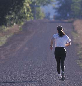 Woman running on road with trees in front of her